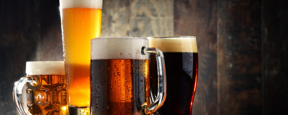 Four glassed of beer on wooden background.