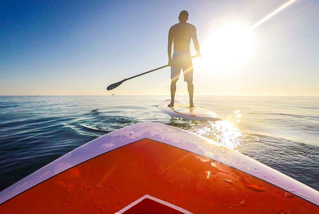 Picture taken from that vantage of a paddleboat behind another man on a paddleboard with the sun in front of him on Lake Michigan - What to do in South Haven