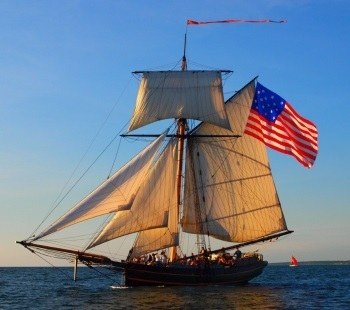 Picture of Friends Good Will sailing on Lake Michigan with full sails and the American flag flying full - What to do in South Haven