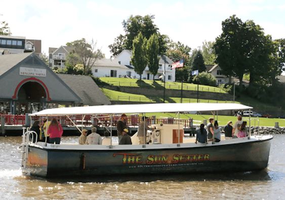 Picture of Sun Setter boat loaded with passengers going down the Black River in front of the South Haven Black River pavilion - What to do in South Haven