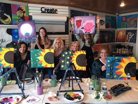 Picture of several artists holding their paintings at Tipsy Brush Studios - What to do in South Haven